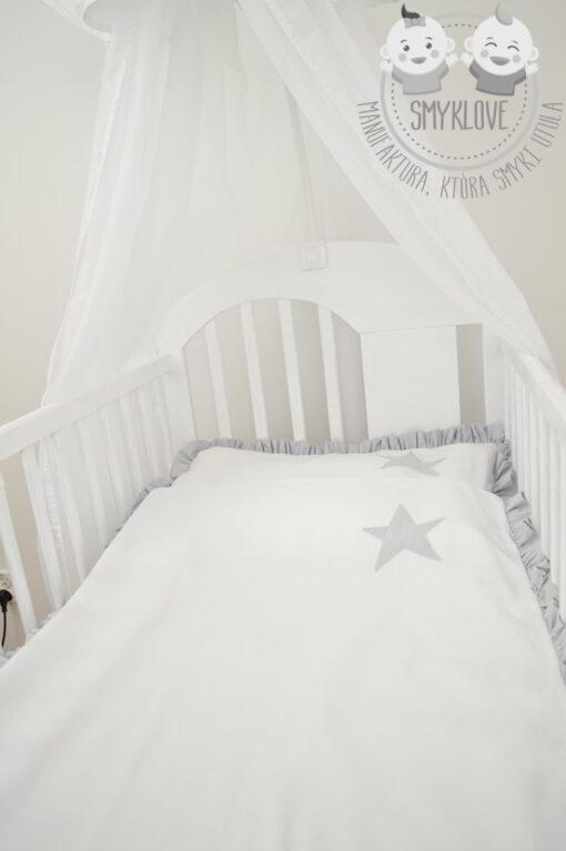 Widok z boku na pościel do łóżeczka z falbanką