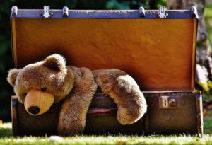 Zdjęcie walizki z pluszowym misiem przygotowaną na wakacje z niemowlakiem
