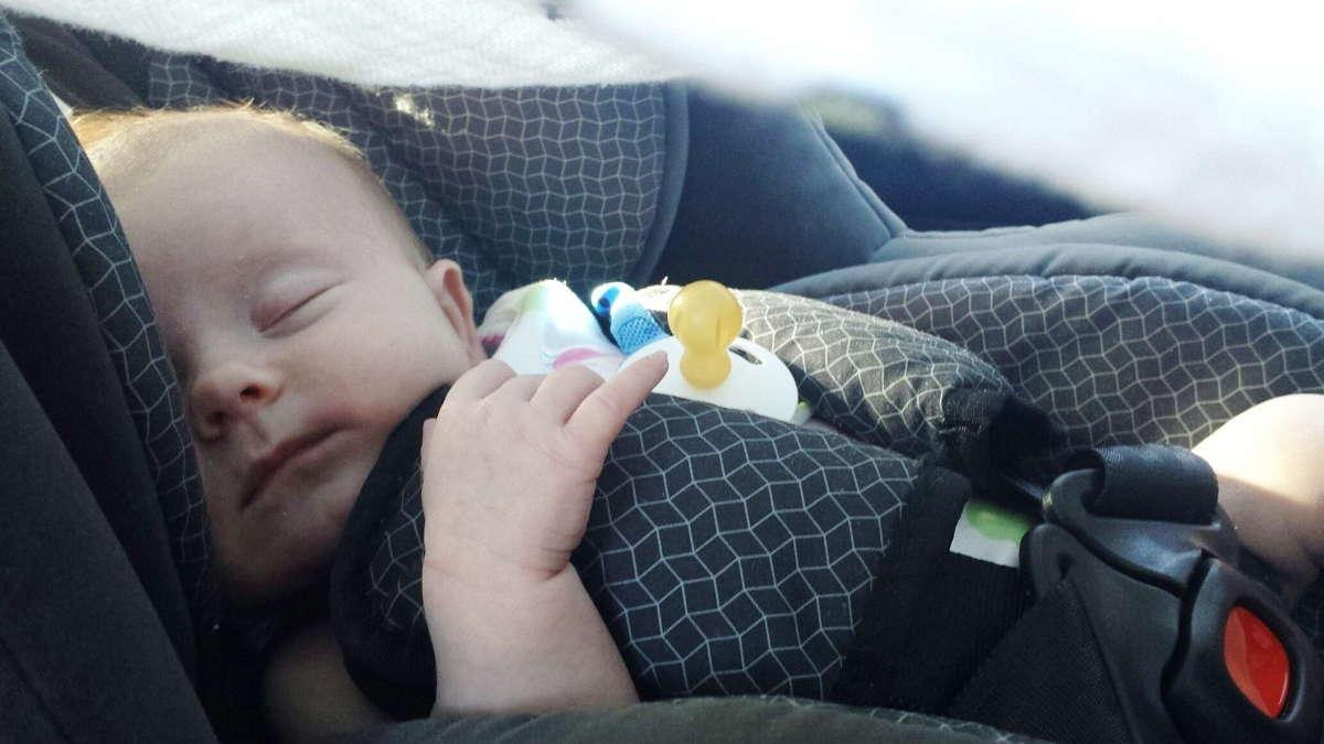 Zdjęcie z niemowlkaiem śpiącym w foteliku samochodowym