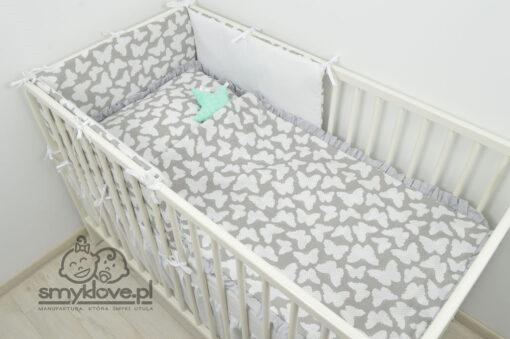 Pościel w motylki z szarą falbanką w łóżeczku niemowlęcym
