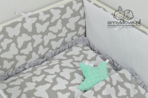 Zbliżenie na ochraniacz i szarą falbankę w pościeli w motylki do łóżeczka