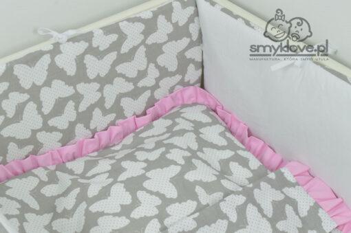 Zbliżenie na różową falbankę w pościeli do łóżeczka w motylki