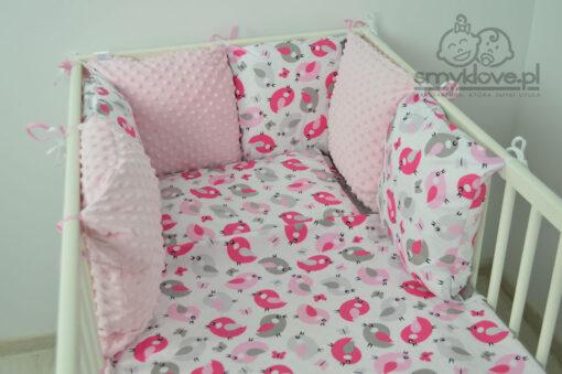 Zbliżenie na kocyk i poduszkę oraz ochraniacz z zestawu do łóżeczka dla dziewczynki