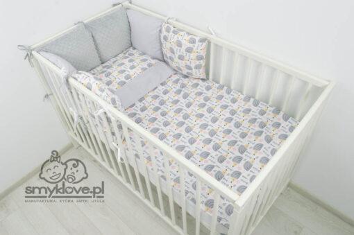 Widok na łóżeczką z pościelą dla niemowlaka w jeżyki z szarym