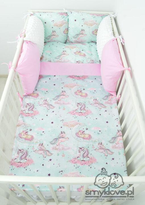 Zdjęcie z góry na pościel do łóżeczka w jednorożce z ochraniaczem na szczebelki z poduszek
